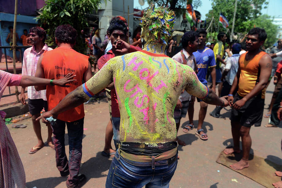 Indian revelers dance to popular Bollywood music tunes during Holi celebrations in Mumbai on March 27, 2013. 'Holi', the festival of colors, is a riotous celebration of the coming of spring and falls on the day after full moon annually in March. Revealers spray colored powder and water on each other with great gusto, whilst adults extend the hand of peace. Photo: INDRANIL MUKHERJEE, AFP/Getty Images / 2013 AFP