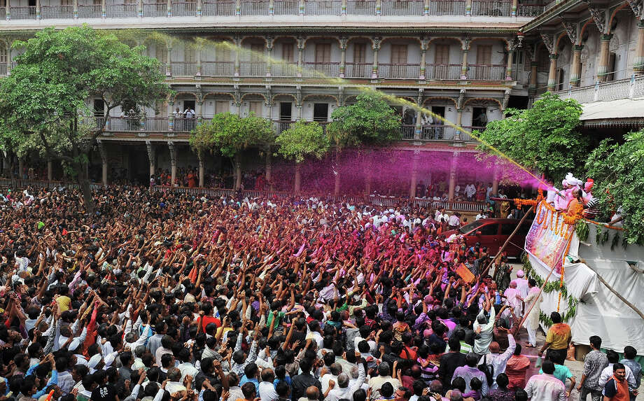 Indian Hindu devotees are sprayed with colored water as they celebrate the 'Holi' festival at the Swaminarayan Temple in Kalupur, Ahmedabad on March 27, 2013. Holi, also called the Festival of Colors, is a popular Hindu spring festival observed in India at the end of the winter season on the last full moon day of the lunar month. Photo: AFP, AFP/Getty Images / 2013 AFP