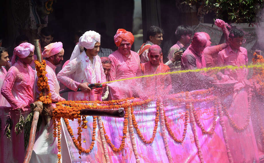 Indian heir to the Kalupur Swaminarayan Temple, Lalji Maharaj Shri Vrajendraprasdaji Maharaj, sprays Hindu devotees with coloured water as they celebrate the 'Holi' festival at the Swaminarayan Temple in Kalupur, Ahmedabad on March 27, 2013. Holi, also called the Festival of Colors, is a popular Hindu spring festival observed in India at the end of the winter season on the last full moon day of the lunar month. Photo: AFP, AFP/Getty Images / 2013 AFP