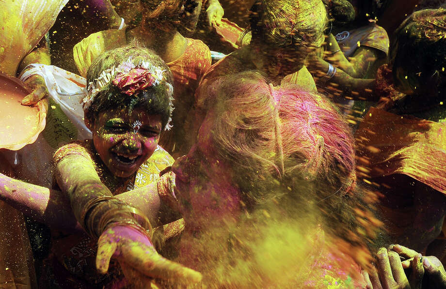Indian school students dance and  play with colored powder on the side of a road during Holi celebrations  in Kolkata on March 27, 2013. Holi, also called the Festival of Colours, is a popular Hindu spring festival observed in India at the end of the winter season on the last full moon day of the lunar month. Photo: DIBYANGSHU SARKAR, AFP/Getty Images / 2013 AFP