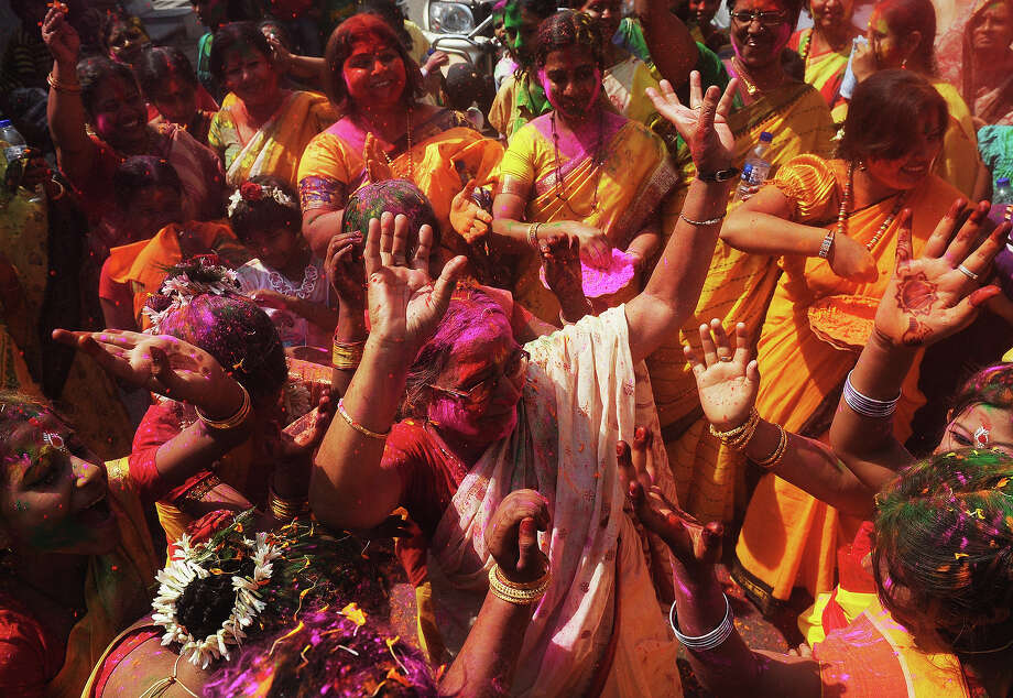 Indian Hindu devotees dance and  play with colored powder on the side of a road during Holi celebrations  in Kolkata on March 27, 2013. Holi, also called the Festival of Colors, is a popular Hindu spring festival observed in India at the end of the winter season on the last full moon day of the lunar month. Photo: DIBYANGSHU SARKAR, AFP/Getty Images / 2013 AFP