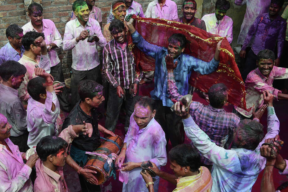 Indian Hindu devotees their faces smeared with colored powder dance during Holi festival celebrations in Amritsar on March 27, 2013. 'Holi', the Festival of Colors, is a popular Hindu spring festival observed in India and Nepal at the end of winter season on the last full moon day of the lunar month. Photo: NARINDER NANU, AFP/Getty Images / 2013 AFP