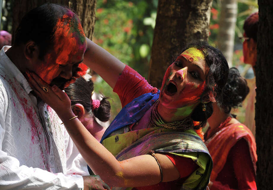 Indian revelers cover each other with colored powder look on during Holi festival celebrations in Siliguri on March 27, 2013. 'Holi', the Festival of Colors, is a popular Hindu spring festival observed in India and Nepal at the end of winter season on the last full moon day of the lunar month. Photo: DIPTENDU DUTTA, AFP/Getty Images / 2013 AFP
