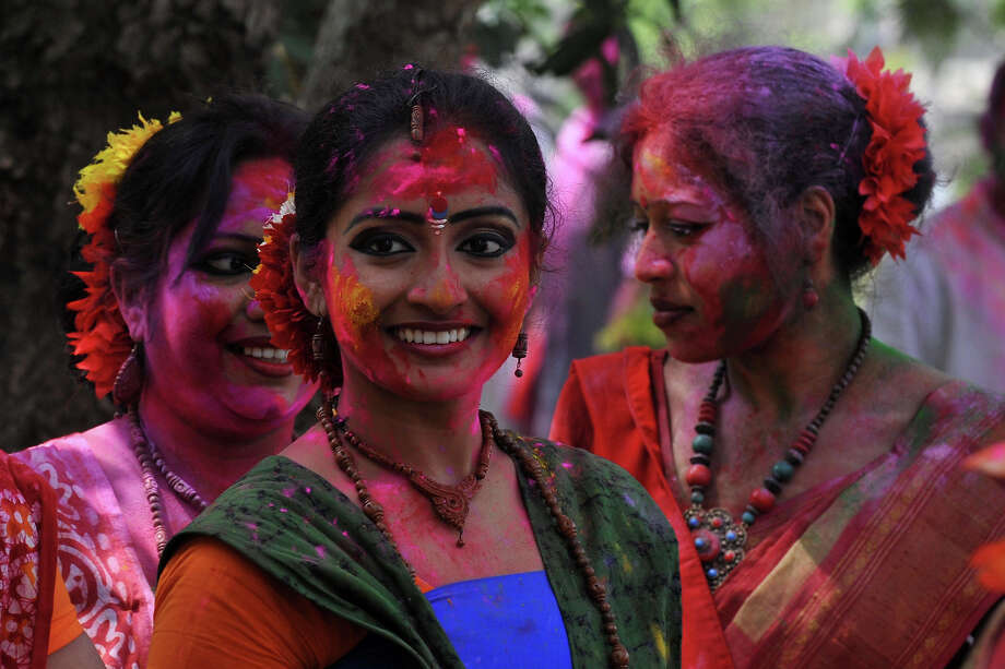 Indian revelers covered with colored powder look on during Holi festival celebrations in Siliguri on March 27, 2013. 'Holi', the Festival of Colors, is a popular Hindu spring festival observed in India and Nepal at the end of winter season on the last full moon day of the lunar month. Photo: DIPTENDU DUTTA, AFP/Getty Images / 2013 AFP