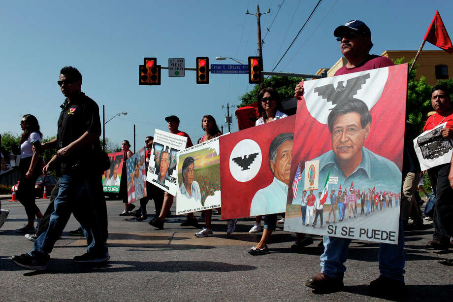 Joel Ortiz, far right, marches with his wife, Esmeralda Ortiz, and daughter, Leah Ortiz, 14, as they carry paintings by his brother, Abel Ortiz, in honor of Ortiz who passed away, as marchers turn off Cesar E. Chavez Blvd. onto South Flores Street during the Cesar E. Chavez March for Justice in San Antonio on Saturday, March 31, 2012. Photo: Lisa Krantz, SAN ANTONIO EXPRESS-NEWS / SAN ANTONIO EXPRESS-NEWS