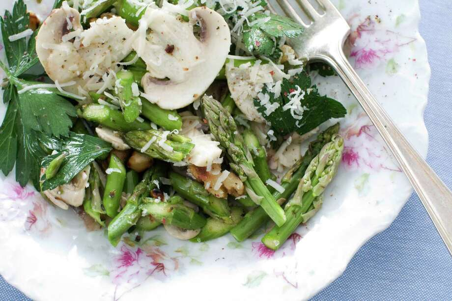 In this image taken on March 11, 2013, a raw asparagus, mushroom and parsley salad with nuts is shown served on a plate in Concord, N.H. (AP Photo/Matthew Mead) Photo: Matthew Mead