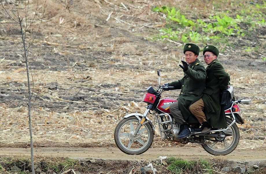 "North Korean military personnel share a ride on a motorscooter near the shoreline of the Yalu River, some 70 kms north of Dandong in northeast China's Liaoning province which lies across the river from the North Korean border town of Siniuju on November 24, 2010. Chinese state media coverage of the Korean peninsula shelling incident has avoided criticising Beijing's close ally Pyongyang and even said the episode showed North Korea's ""toughness"" after the reclusive communist state fired a deadly barrage of artillery shells onto a South Korean island on November 23 in one of the most serious border incidents since the 1950-1953 war, sparking global condemnation of Pyongyang. Photo: FREDERIC J. BROWN, AFP/Getty Images / 2010 AFP"