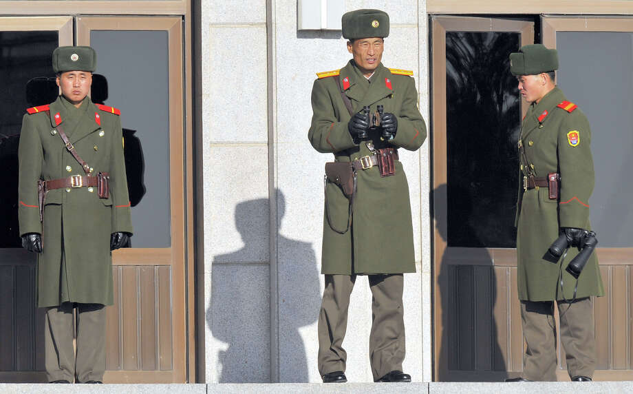North Korean military officer (C) uses binoculars to look towards the South Korean side at the border village of Panmunjom on December 6, 2008.  North Korea said 5 December it would not recognise Japan as a member of six-nation nuclear disarmament talks since Tokyo refuses to provide its share of energy aid promised to Pyongyang. Photo: KIM JAE-HWAN, AFP/Getty Images / 2012 AFP