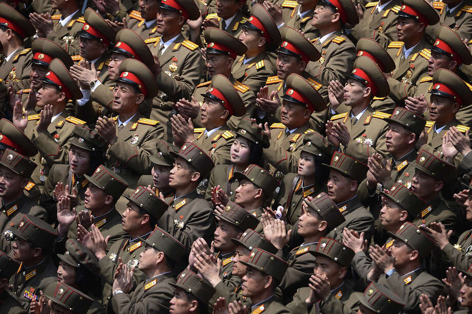 North Korean military applaud during an official ceremony attended by leader Kim Jong-Un at a stadium in Pyongyang on April 14, 2012. North Korea will mark the 100th birthday of their leader Kim Il-Sung on April 15. Photo: PEDRO UGARTE, AFP/Getty Images / 2012 AFP