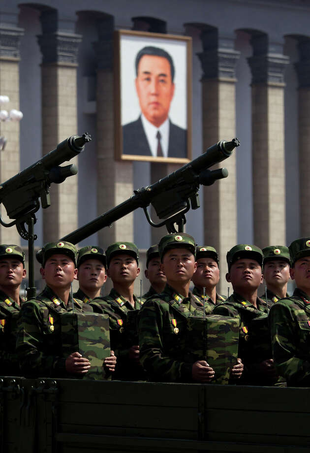 North Korean military ride past a portrait of former leader Kim Il-Sung during a military parade to mark 100 years since the birth of the country's founder Kim Il-Sung in Pyongyang on April 15, 2012.  The commemorations came just two days after a satellite launch timed to mark the centenary fizzled out embarrassingly when the rocket apparently exploded within minutes of blastoff and plunged into the sea. Photo: ED JONES, AFP/Getty Images / 2012 AFP