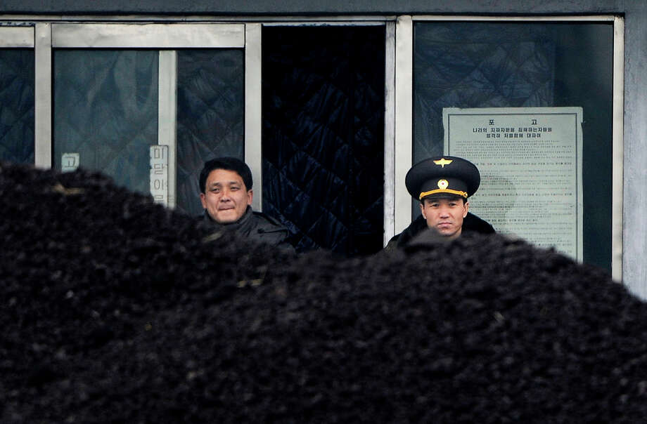 This picture taken on December 14, 2012 from China's northeastern city of Dandong, looking across the border, shows a North Korean military officer (R) and a North Korea man (L) standing behind a pile of coal along the banks of the Yalu River in the northeast of the North Korean border town of Siniuju.  China is North Korea's biggest trading partner by far, and most of the business passes through Dandong in northeastern China, where lorries piled high with tyres and sacks are processed at the customs post. Photo: AFP, AFP/Getty Images / 2012 AFP