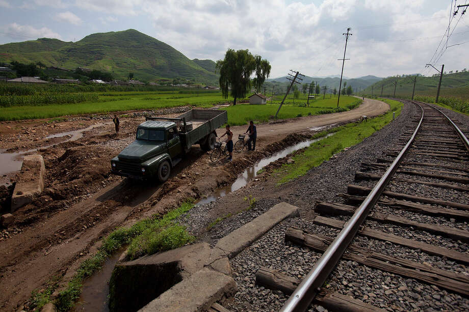 In this Monday, Aug 13, 2012 photo, a North Korean military truck and men on bicycles try to pass through a road, washed out during July 2012 flooding, in Songchon County, North Korea. Twin typhoons are renewing fears of a humanitarian crisis in North Korea, where poor drainage, widespread deforestation and fragile infrastructure can turn even a routine rainstorm into a catastrophic flood. Photo: David Guttenfelder, ASSOCIATED PRESS / AP2012