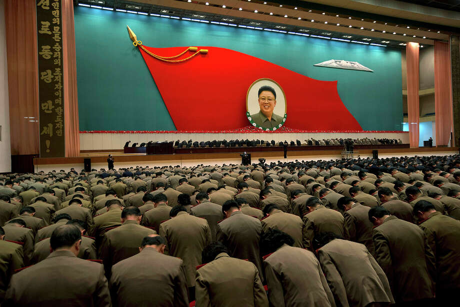"North Korean military officers bow at an image of late North Korean leader Kim Jong Il during a national meeting of top party and military officials on the eve of Kim's first death anniversary in Pyongyang, North Korea, Sunday, Dec. 16, 2012. Large characters on vertical banner at left read  ""Hurrah to the Workers' Party of Korea."" Photo: Ng Han Guan, ASSOCIATED PRESS / AP2012"