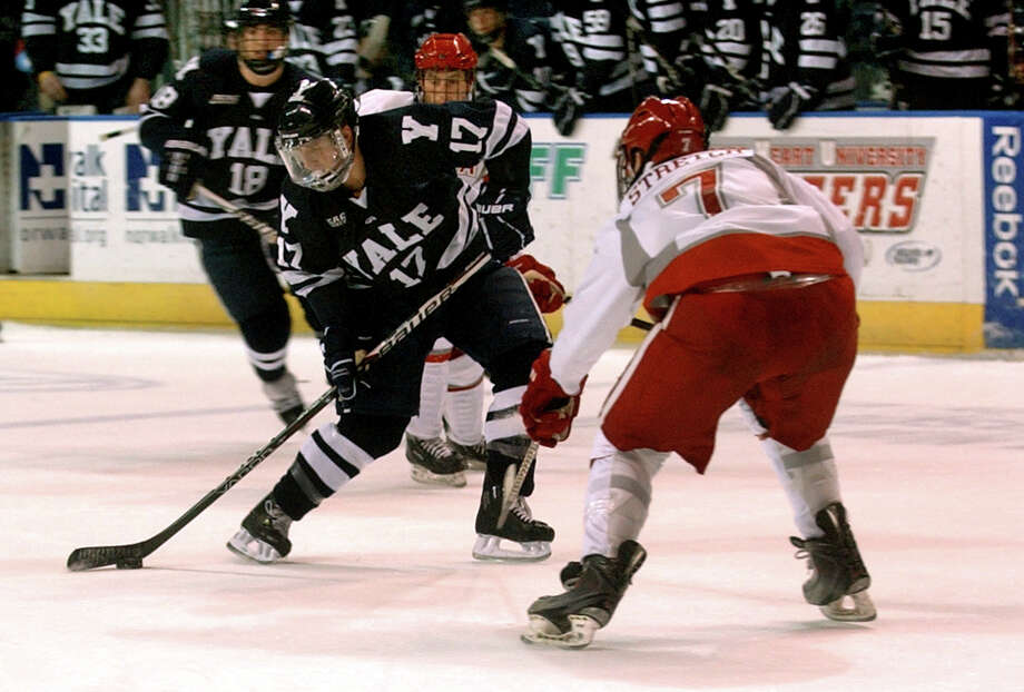 Yale's #17 Andrew Miller, left, drives the puck as Sacred Heart University's #7 Mitchell Stretch defends, during men's ice hockey action at the Webster Bank Arena in Bridgeport, Conn. on Tuesday November 22, 2011. Miller sent this puck in for a goal. Photo: Christian Abraham / Connecticut Post