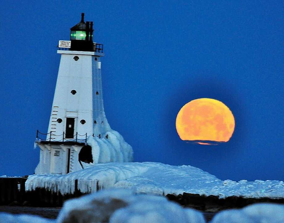 "A ""Crow Moon"" sets over Lake Michigannear the Ludington North Breakwater Light. According to the Farmer's Almanac, northern Indian tribes called the March full moon the Crow Moon because the cawing of the crows signaled the end of winter and start of spring. Photo: Associated Press"