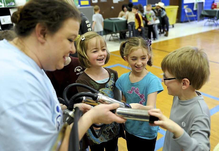 Pull my finger: Spottsville (Ky.) Elementary students Libby Butler (left), Jada Voyles and Brayden Butler giggle as a milking machine held by parent volunteer Beth Frederick tries to milk their fingers. Photo: Darrin Phegley, Associated Press
