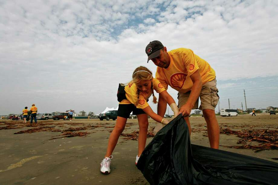 "Shell Oil Company volunteers Morgan Barnett (left) and Danny Barnett help clean up the San Luis Pointe beachfront in Galveston during ""Adopt-A-Beach"" Day on Sept. 26, 2009. Shell volunteers, Morgan (12) and Danny Barnett, help clean up the San Luis Pointe beachfront in Galveston during the ""Adopt-A-Beach"" day Saturday, Sept. 26, 2009, in Galveston.  More than 380,000 Adopt-A-Beach volunteers have removed 7,300 tons of trash from Texas beaches since the first cleanup in 1986.  The Texas General Land Office Adopt-A-Beach program is a volunteer effort held twice a year at locations along the Texas coast.  Some 300 Shell volunteers showed up to form one of the largest Adopt-A-Beach volunteer teams in the state.    ( Michael Paulsen / Chronicle ) Photo: Houston Chronicle, Staff"