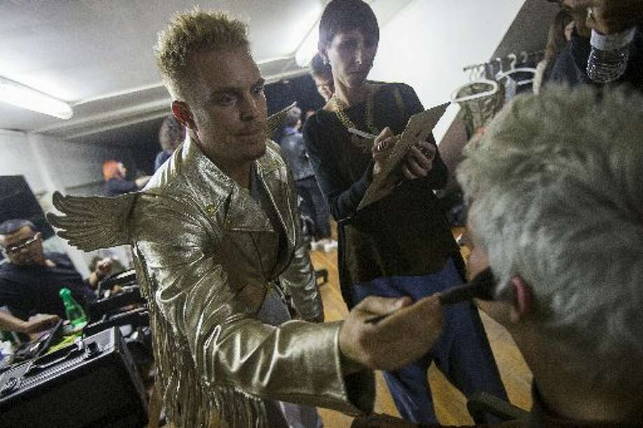 Adam Love, left, event host of fashion collective Underground Fashion Week, puts makeup on Daniel Goodwyn backstage.
