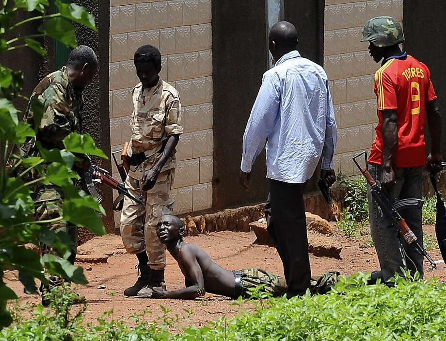 Thievery alleged:Seleka coalition rebels arrest a suspected looter claiming to a member of their movement outside a ransacked house in Bangui, Central African Republic. The African Union ordered sanctions against rebel leaders who captured the capital over the weekend. Photo: Sia Kambou, AFP/Getty Images