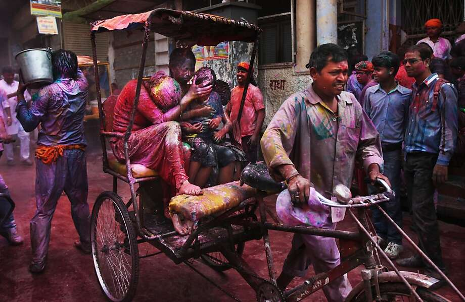 A woman soaked with dye covers the face of a child as they ride a rickshaw past people celebrating the Holi festival of colors outside Banke Bihari temple in Vrindavan, India. Photo: Altaf Qadri, Associated Press