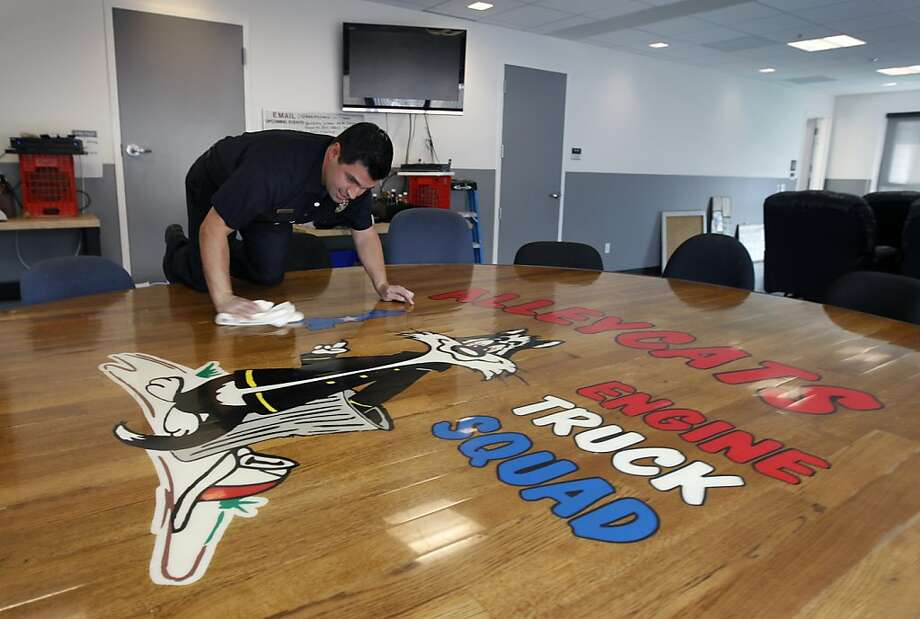 "Firefighter Geoffrey Quesada polishes the station's handmade, wooden table bearing the firehouse's ""Alleycats"" logo. Photo: Paul Chinn, The Chronicle"