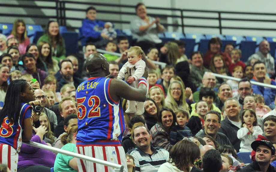 """Big Easy"" of the Harlem Globetrotters holds a baby in the audience,  Emma Kathleen Gonzalez, 10 months old, of New Milford, during the Harlem Globetrotters game at the O'Neill Center at Western Connecticut State University in Danbury, Conn. on Tuesday, March 26, 2013.  Hundreds of students and families crowded the arena to watch the basketball comedy act perform its interactive routine. Photo: Tyler Sizemore / The News-Times"