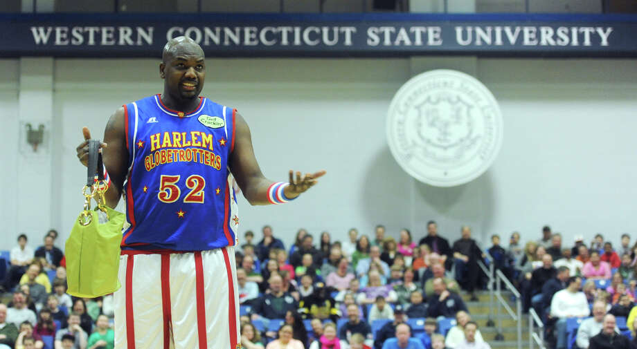 """Big Easy"" carries a ladies handbag during the Harlem Globetrotters game at the O'Neill Center at Western Connecticut State University in Danbury, Conn. on Tuesday, March 26, 2013.  Hundreds of students and families crowded the arena to watch the basketball comedy act perform its interactive routine. Photo: Tyler Sizemore / The News-Times"