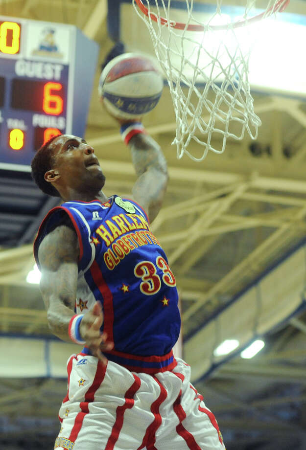 """""""Bull"""" slam dunks during the Harlem Globetrotters game at the O'Neill Center at Western Connecticut State University in Danbury, Conn. on Tuesday, March 26, 2013.  Hundreds of students and families crowded the arena to watch the basketball comedy act perform its interactive routine. Photo: Tyler Sizemore / The News-Times"""