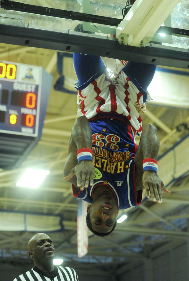 """Bull"" hangs upside down from the hoop during the Harlem Globetrotters game at the O'Neill Center at Western Connecticut State University in Danbury, Conn. on Tuesday, March 26, 2013.  Hundreds of students and families crowded the arena to watch the basketball comedy act perform its interactive routine. Photo: Tyler Sizemore / The News-Times"