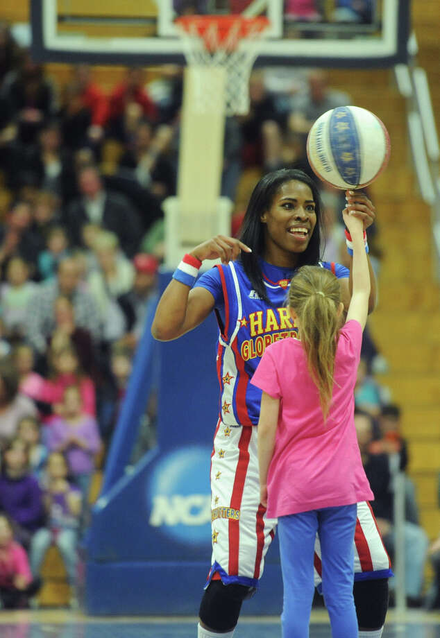 """TNT"" helps a young fan spin a basketball on her finger during the Harlem Globetrotters game at the O'Neill Center at Western Connecticut State University in Danbury, Conn. on Tuesday, March 26, 2013.  Hundreds of students and families crowded the arena to watch the basketball comedy act perform its interactive routine. Photo: Tyler Sizemore / The News-Times"