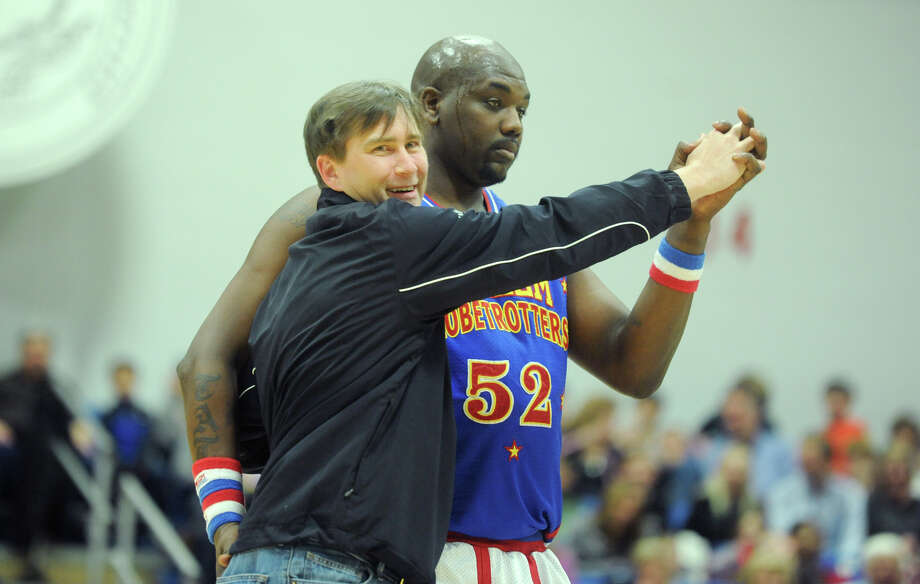 """Big Easy"" tango dances with Jim Dormer, of Wilton, during the Harlem Globetrotters game at the O'Neill Center at Western Connecticut State University in Danbury, Conn. on Tuesday, March 26, 2013.  Hundreds of students and families crowded the arena to watch the basketball comedy act perform its interactive routine. Photo: Tyler Sizemore / The News-Times"