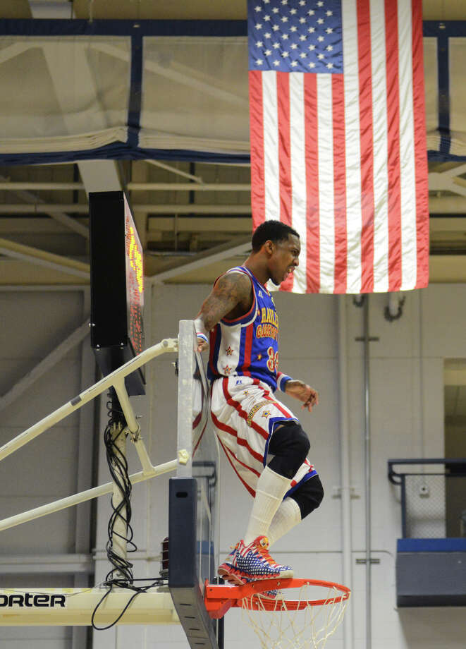 """Bull"" dances on top of the hoop during the Harlem Globetrotters game at the O'Neill Center at Western Connecticut State University in Danbury, Conn. on Tuesday, March 26, 2013.  Hundreds of students and families crowded the arena to watch the basketball comedy act perform its interactive routine. Photo: Tyler Sizemore / The News-Times"