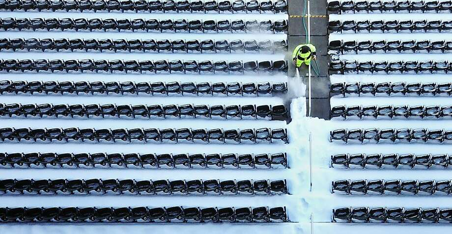 Patrick Wenzel sprays thick layers of snow and ice off the seats of Target Field. Crews used high-pressure heated water to clean snow and ice from the seats of the baseball field in preparation for the Minnesota Twins' opening day game against the Detroit Tigers on April 1. Photo: Ben Garvin, Associated Press
