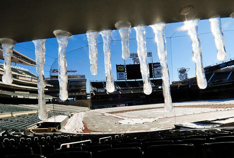 Getting ready for Opening Day 2013: The grass and infield at Target Field in Minneapolis are heated and covered with a tarp, but the seats have to be cleared after a winter's accumulation.  Photo: Ben Garvin, Associated Press