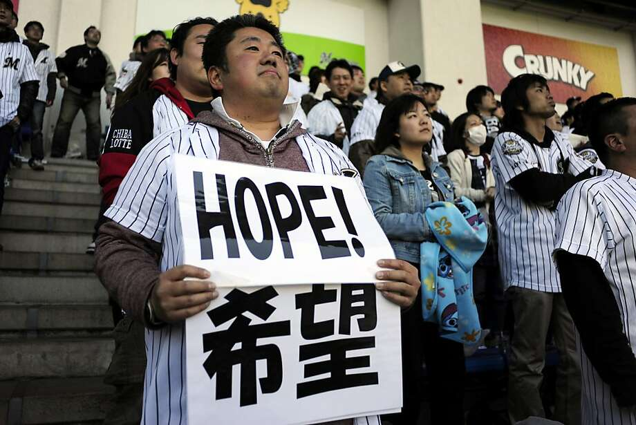 A fan of the Chiba Lotte Marines holds a sign supporting the earthquake victims during Opening Day in Chiba, Japan on April 12, 2011. Photo: Keith Bedford, NYT