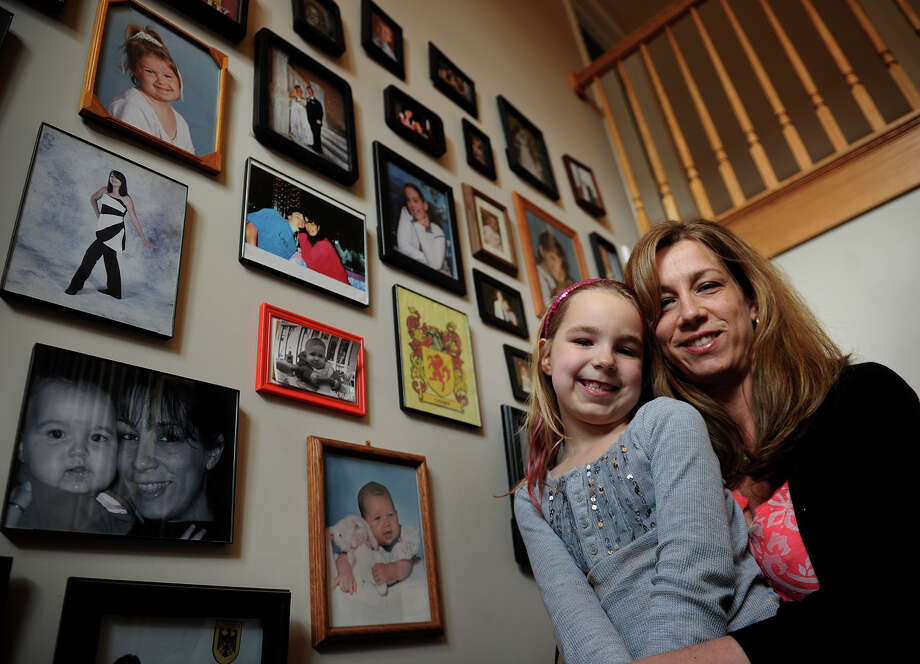 Candace Linnen and her daughter Madison, 7, by their wall of family photos at their home in Shelton, Conn. on March 26, 2013. Photo: Brian A. Pounds / Connecticut Post