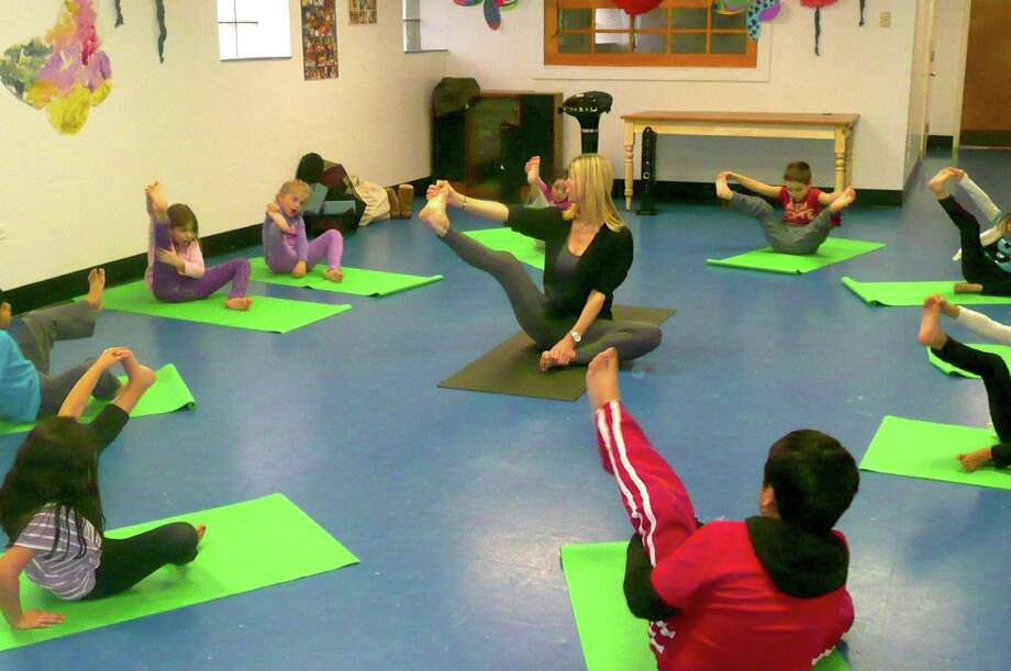 "YogiSays teacher Brooke de Weaver, or ""Miss Brooke"" as she is known, takes various yoga positions and her students at the Byram Archibald Neighborhood Center do their best to follow. Photo: Anne W. Semmes"