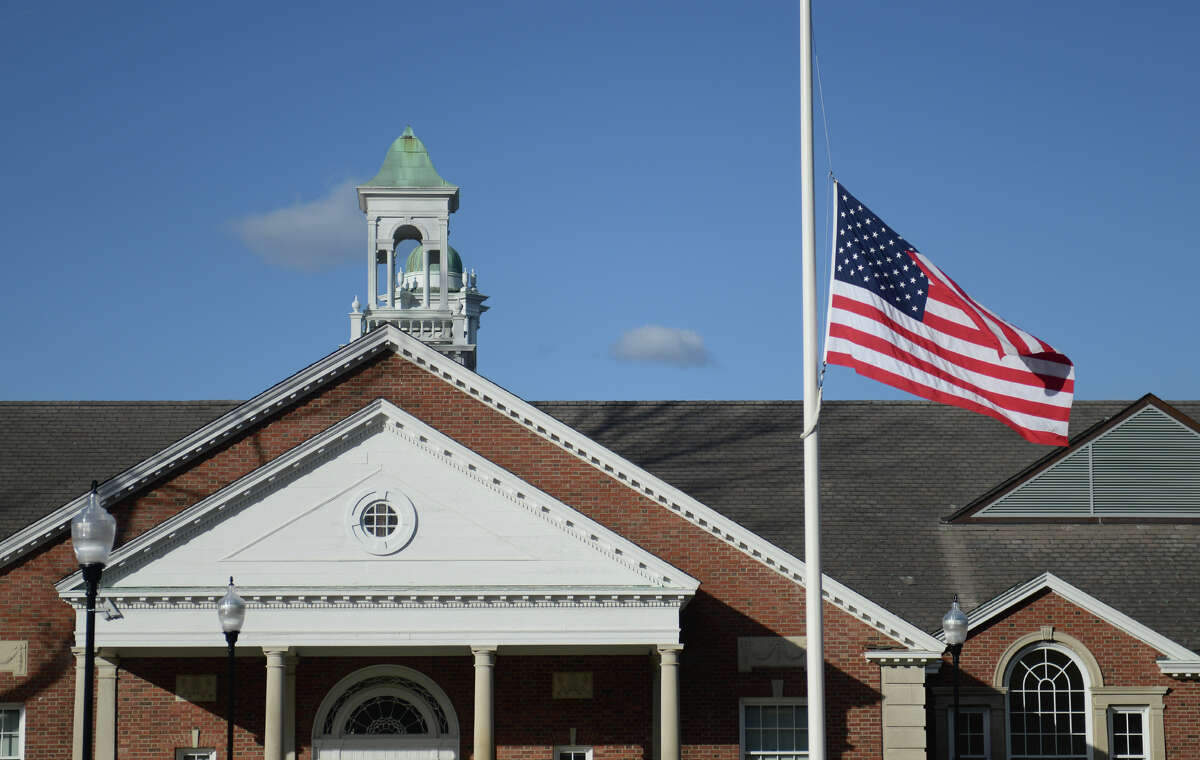 A flag at half-mast waves in front of the Newtown Municipal Center during the state police debriefing for families involved in the Sandy Hook shooting in Newtown, Conn. on Wednesday, March 27, 2013.