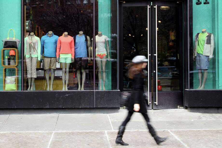 FILE - In this Tuesday, March 19, 2013 file photo,  a woman walks past the Lululemon Athletica store at Union Square in New York. Lululemon says no demonstrations of yoga positions or otherwise are needed to return its pricey black yoga pants that the company pulled from shelves for being too sheer. The yoga gear maker?s policy statement comes after a New York Post report that was widely circulated by the media recounted one woman?s tale of being asked to bend over when trying to return some pants to prove they were sheer. (AP Photo/Mary Altaffer) Photo: Mary Altaffer, STF / AP