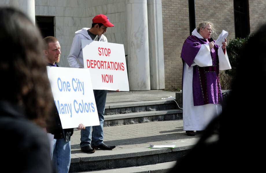 Meghan Vesel, right, of The Brazilian Immigrant Center, speaks at a prayer vigil on the steps of the Danbury Public Library Wednesday, March 27, 2013, in remembrance of local immigrant families who have been affected by deportation and detention. Photo: Carol Kaliff / The News-Times