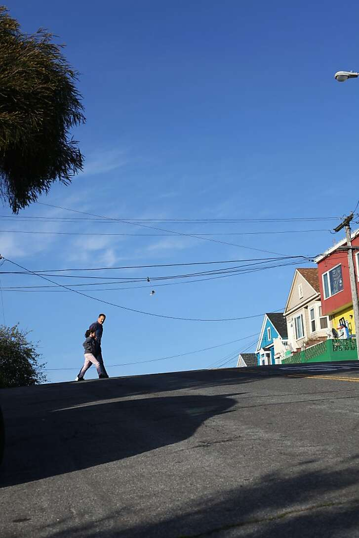 Two pedestrians cross Paris Street heading up the Excelsior Heights hill on March 24, 2013 in San Francisco, Calif.