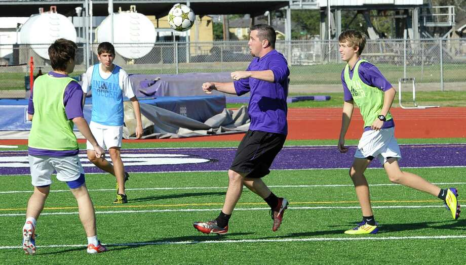 "The Port Neches-Groves High School boys soccer team is one of the best teams in the area.  They were practicing Thursday afternoon, February 14, 2013, at  ""The Reservation."" Chad Luttrull, middle, who is their head coach, mixes it up with several of his players as they run through a drill. Their next game will be on Friday when they host Ozen at 5:30p.m.  Dave Ryan/The Enterprise Photo: Dave Ryan"