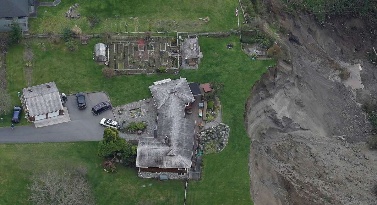 In this aerial photo, a house sits near the edge of a landslide, near Coupeville, Wash. on Whidbey Island, Wednesday, March 27, 2013.