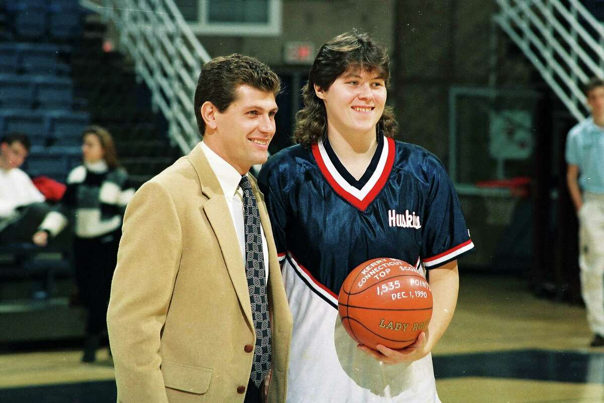 University of Connecticut coach Geno Auriemma stands with player Kerry Bascomb as Bascomb at a presentation for Bascomb's becoming the all-time leading scorer for the UConn women's basketball team, Storrs, CT, 1991. (Photo by Bob Stowell/Getty Images)