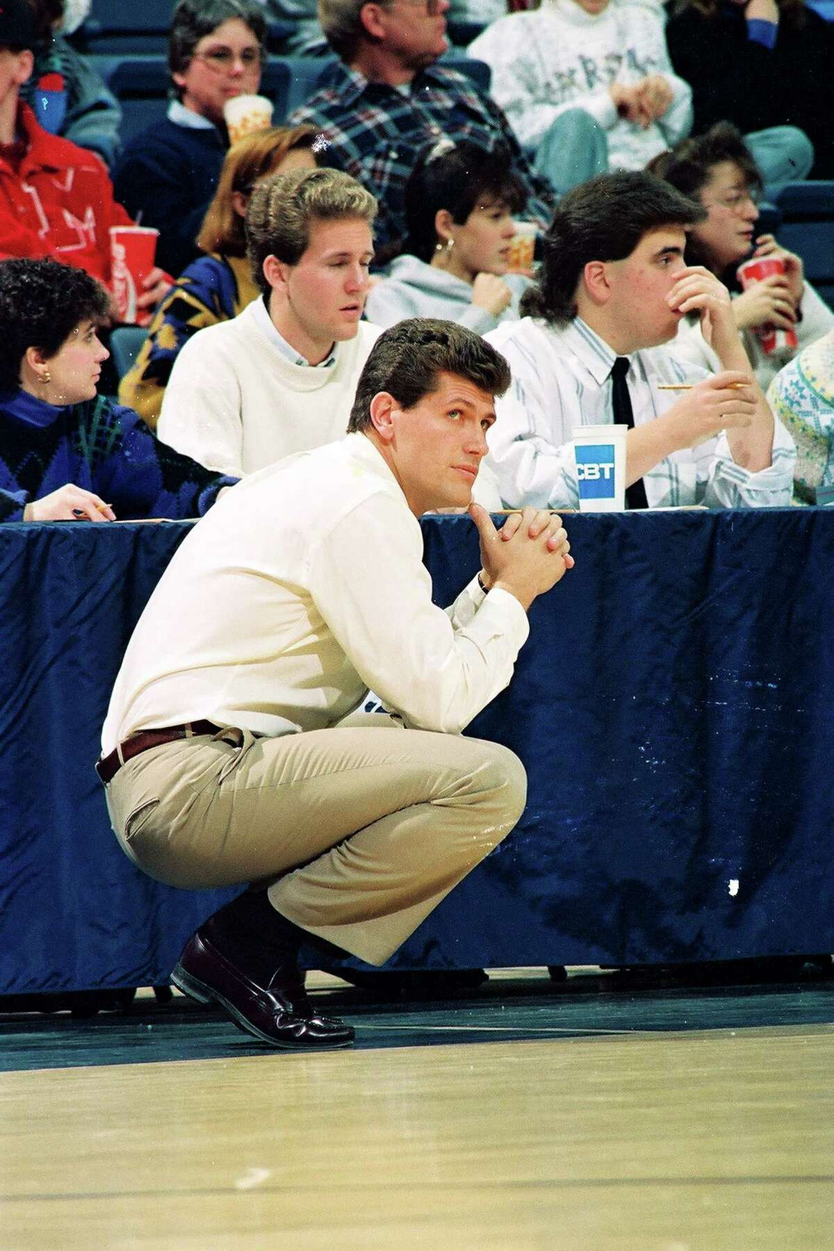 University of Connecticut coach Geno Auriemma watches the action, while crouched on the sideline, Gampel Pavilion, Storrs, CT, 1991. (Photo by Bob Stowell/Gety Images)