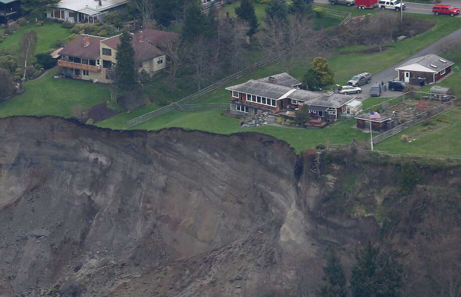 In this aerial photo, a house sits near the edge of a landslide, near Coupeville, Wash. on Whidbey Island, Wednesday, March 27, 2013. The slide severely damaged one home and isolated or threatened more than 30 on the island, about 50 miles north of Seattle in Puget Sound. No one was reported injured in the slide, which happened at about 4 a.m. Wednesday. Photo: Ted S. Warren