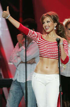 Singer Thalia of Mexico gives a thumb up to the crowd after her performance at the Latin Billboard Awards at the Miami Arena in Miami, Thursday April 28, 2005. (AP Photo/Luis Alvarez) Photo: LUIS ALVAREZ, STR / AP