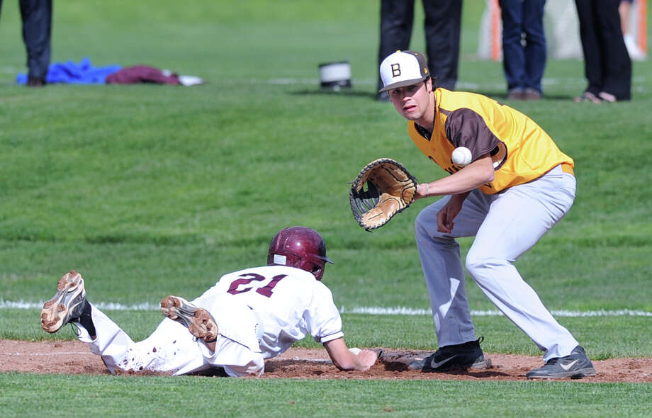 Nick Kono, first baseman for Brunswick School, takes the throw as Gareth Fancher of St. Luke's dives to get safely back  to first on an attempted pick-off play in the baseball game between Brunswick School and St. Luke's at Brunswick School in Greenwich, Thursday afternoon, May 10, 2012. Brunswick won the game, 12-3. Photo: Bob Luckey / Greenwich Time