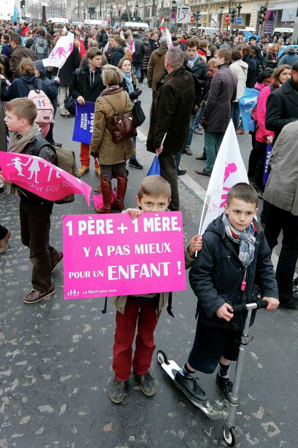 "A boy holds a placard reading "" A father and a mother, nothing it's better for a child"" as thousands of people demonstrate on the Champs-Elysees avenue in Paris on March 24, 2013. Photo: PIERRE VERDY, Getty Images / 2013 AFP"