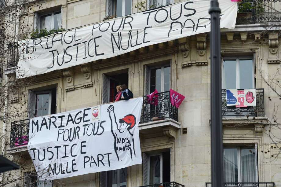 "A picture taken on March 24, 2013 shows banners reading ""Marriage for All, Justice Anywhere"" hanging on balconies during a demonstration against France's gay marriage law in an attempt to block legislation that will allow homosexual couples to marry and adopt children, on March 24, 2013 in Paris. Photo: ERIC FEFERBERG, Getty Images / 2013 AFP"